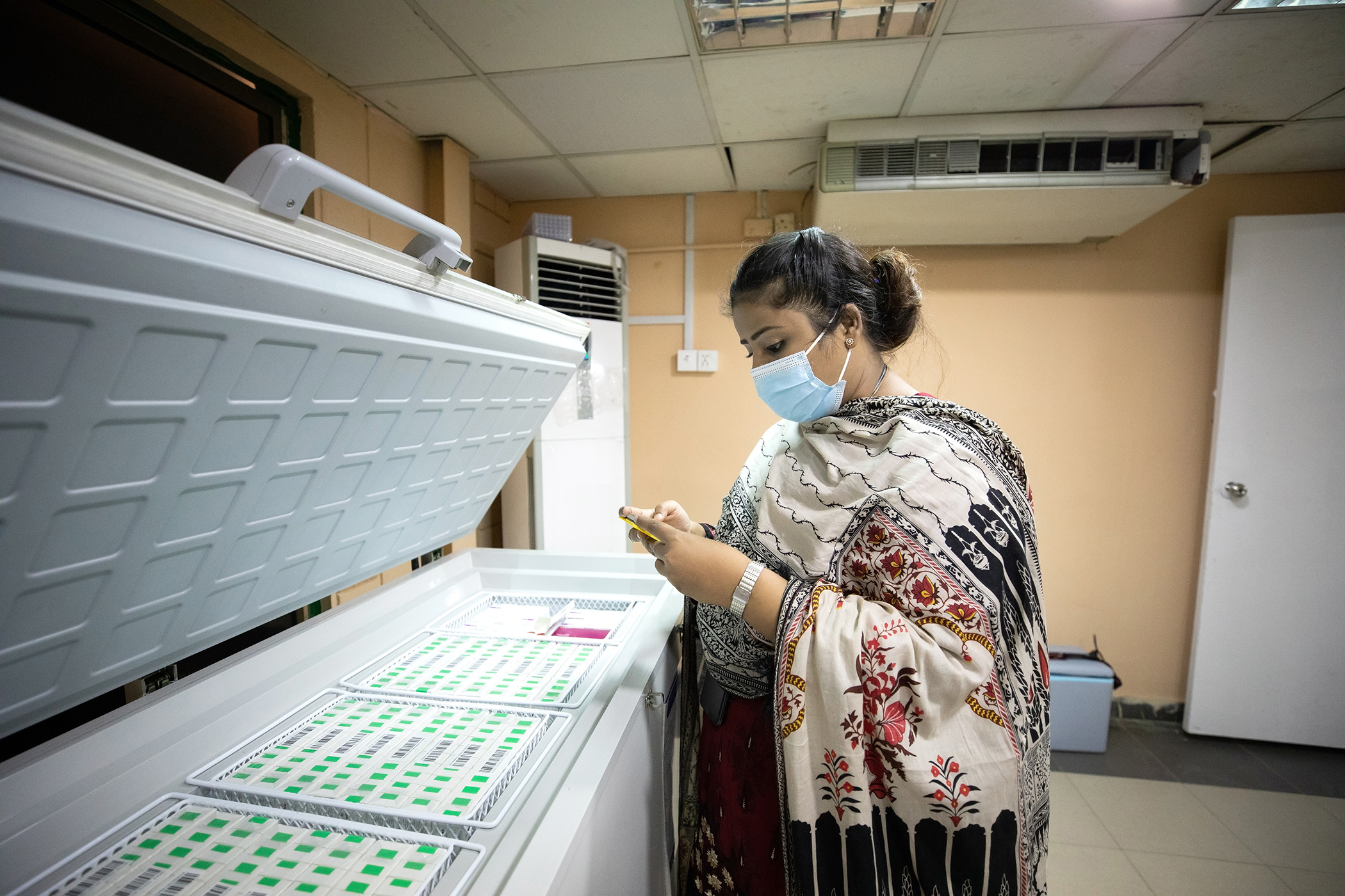 Tahira Bano vérifie la température de réfrigération dans un centre de vaccination à Karachi, au Pakistan, le 5 juin 2021.