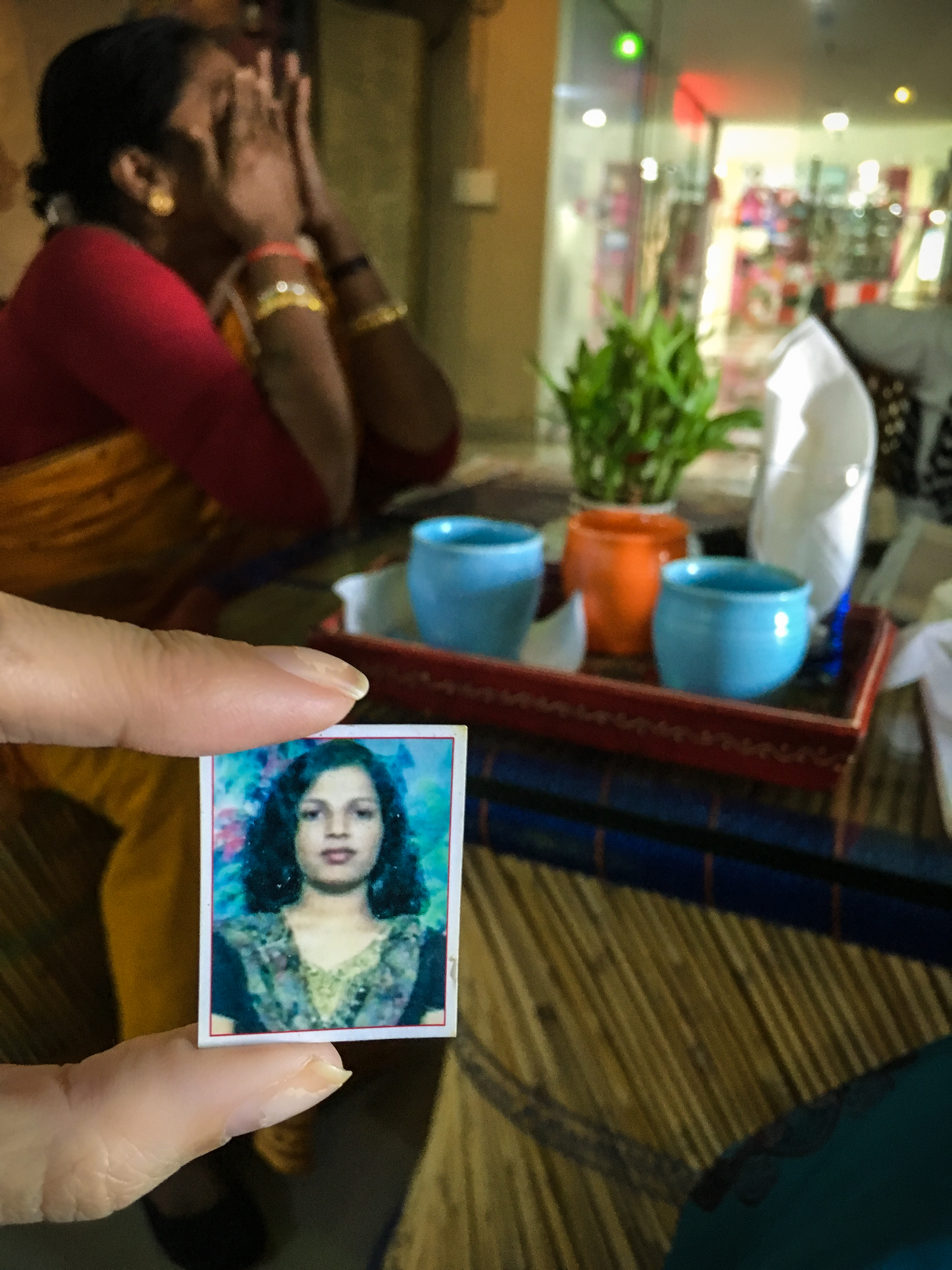Lela holds an old photo of Rani while Kavita stands in the background, overwhelmed by emotions.