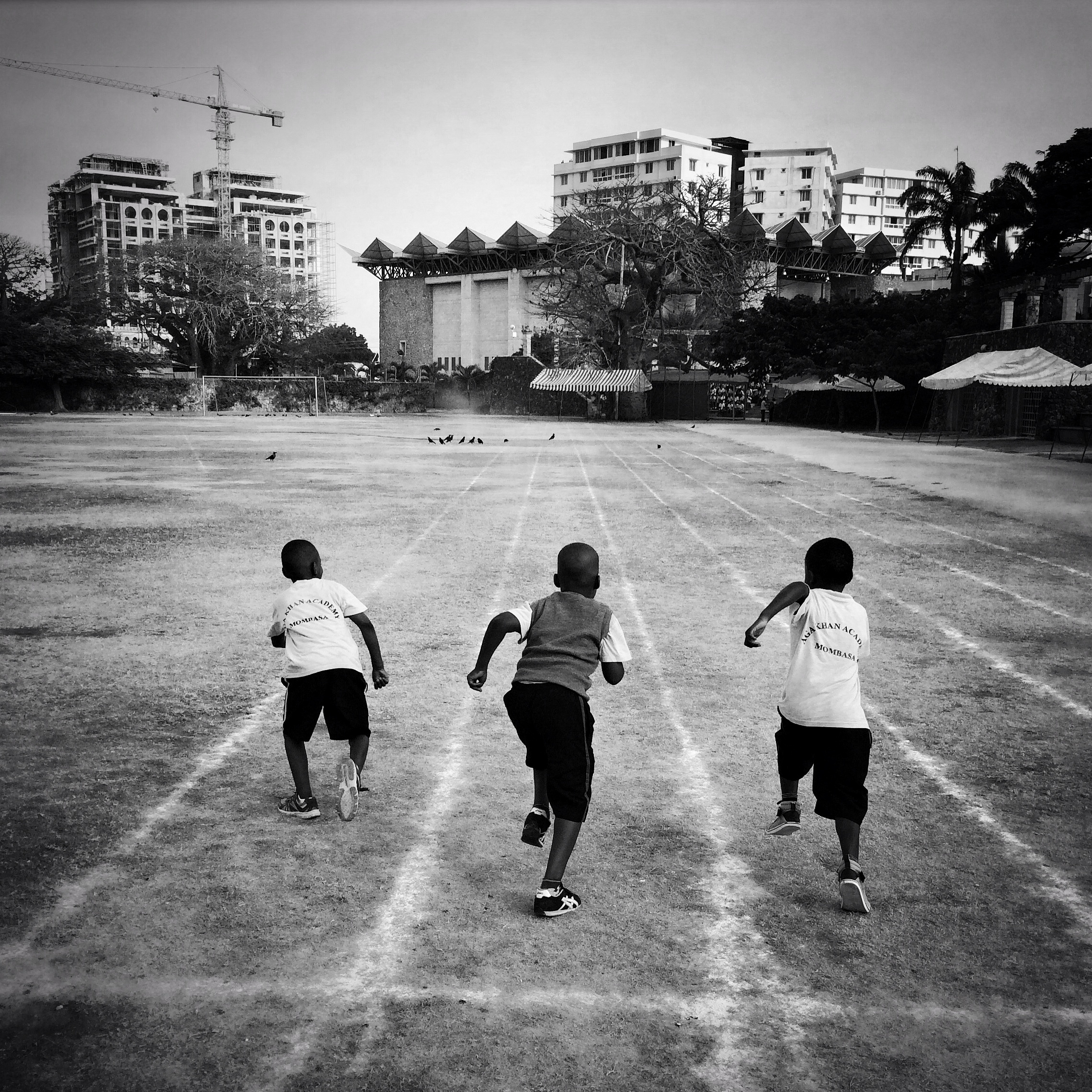 Three boys from the junior school of Aga Khan Academy in Mombasa, Kenya, race on the school's track before the morning assembly. @austin_merrill