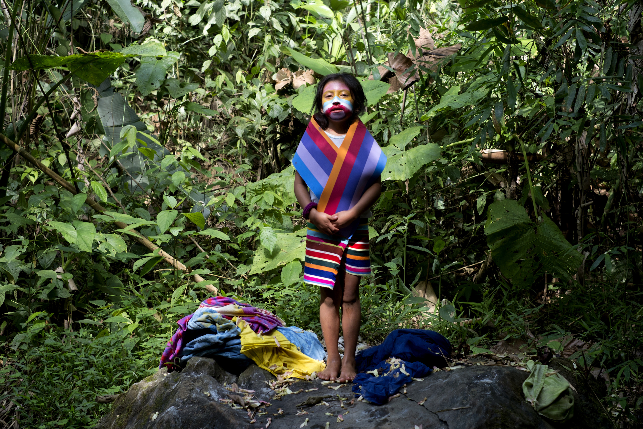 Pumpu (butterfly in English) paints her face and uses the fabrics of her moder to play as if she would be interpreting the myth of the girl who becomes the rainbow. Photo taken in the river Toaochi, Ecuador. (2013) © Emilia Lloret / Native