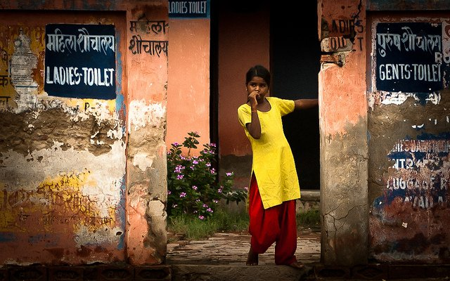 girl standing by toilets in india