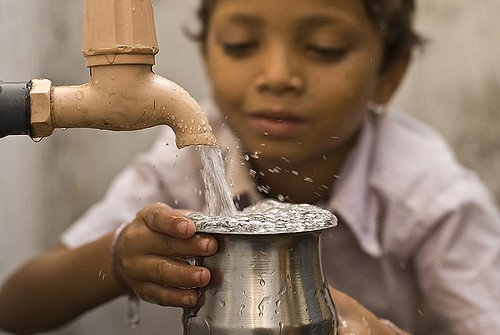 Boy with water in India