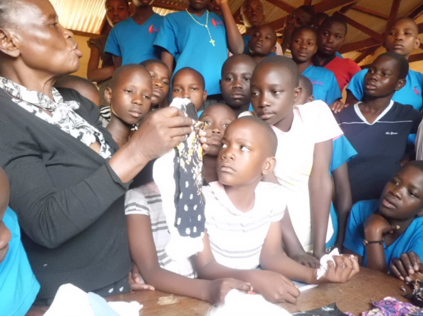 Female head teacher showing girls how to make reusable sanitary pads during a Girl Up Uganda training session.png