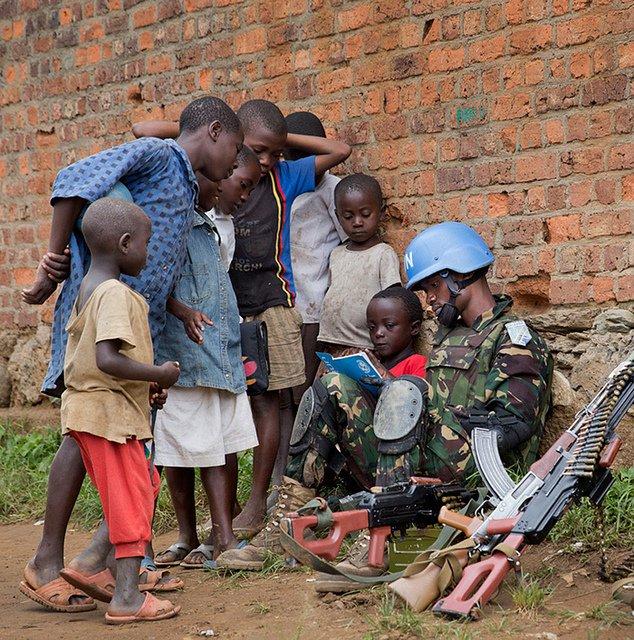 UN peacekeeper helping children to read