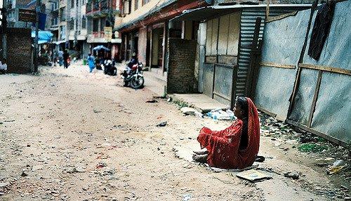 women in red sitting empty street alone