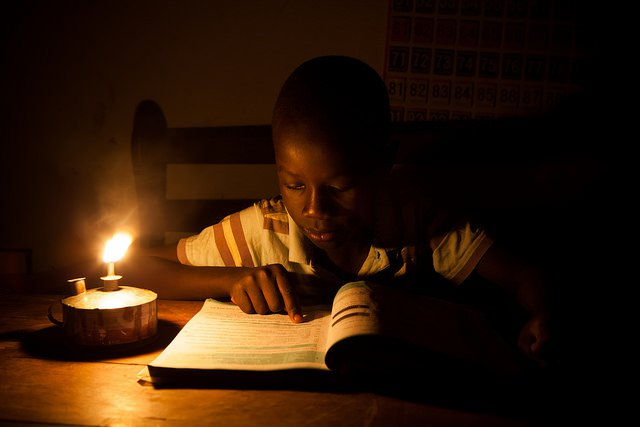 Young boy reading by kerosene lamp