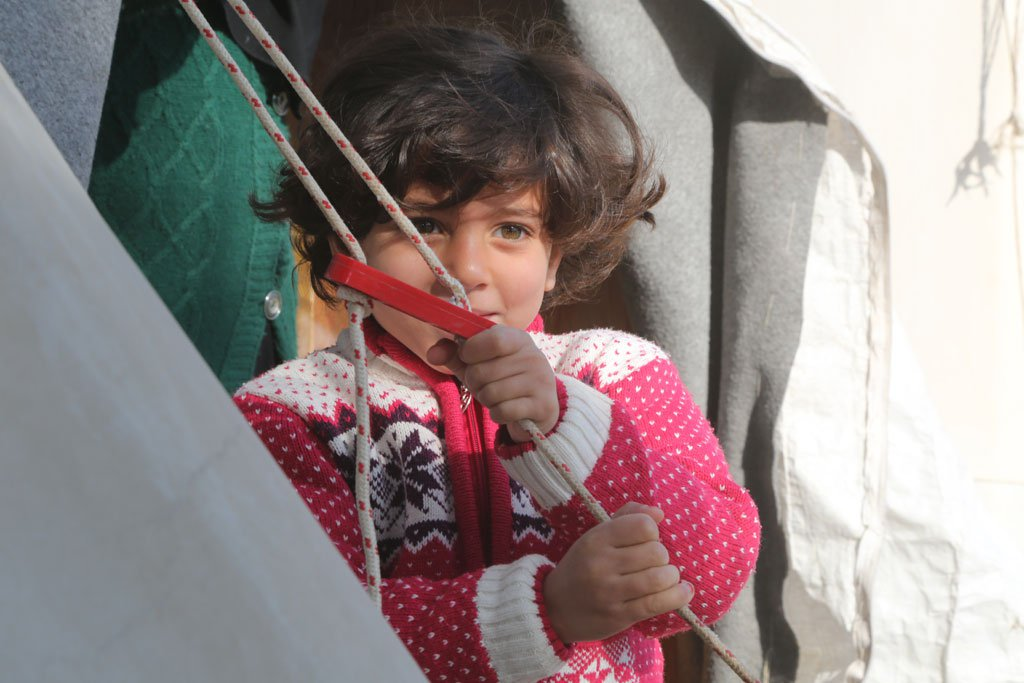 A little Syrian girl outside her family tent in Nizip 1 refugee camp, Gaziantep, southern Turkey