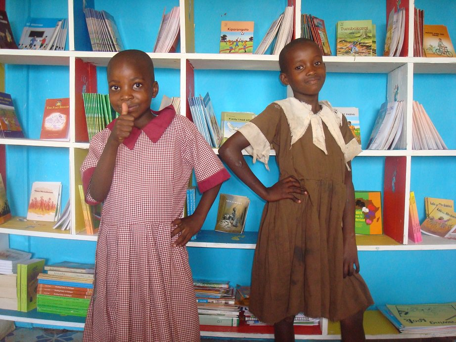 children at the center posing infront of our bookshelf.JPG