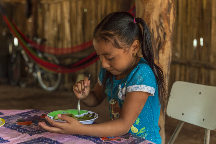 Girl eating a plate of food, World Food Program