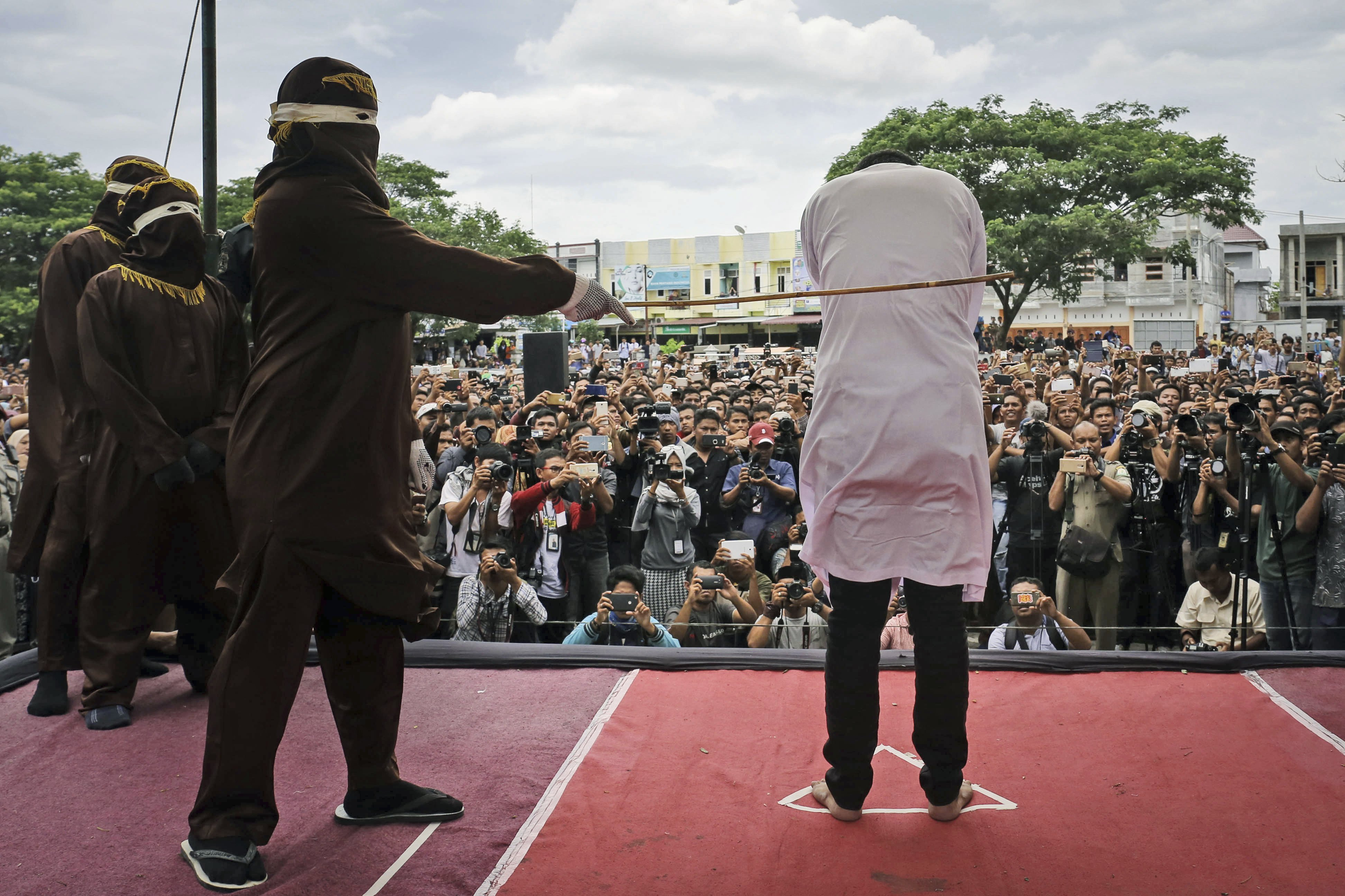 Gay men caned in indonesia.jpg