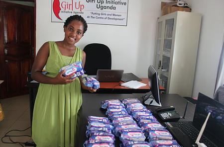 Program Assistant Gloria Komukama with the generous donation of AFRIpad Menstrual kits from HUGs.png