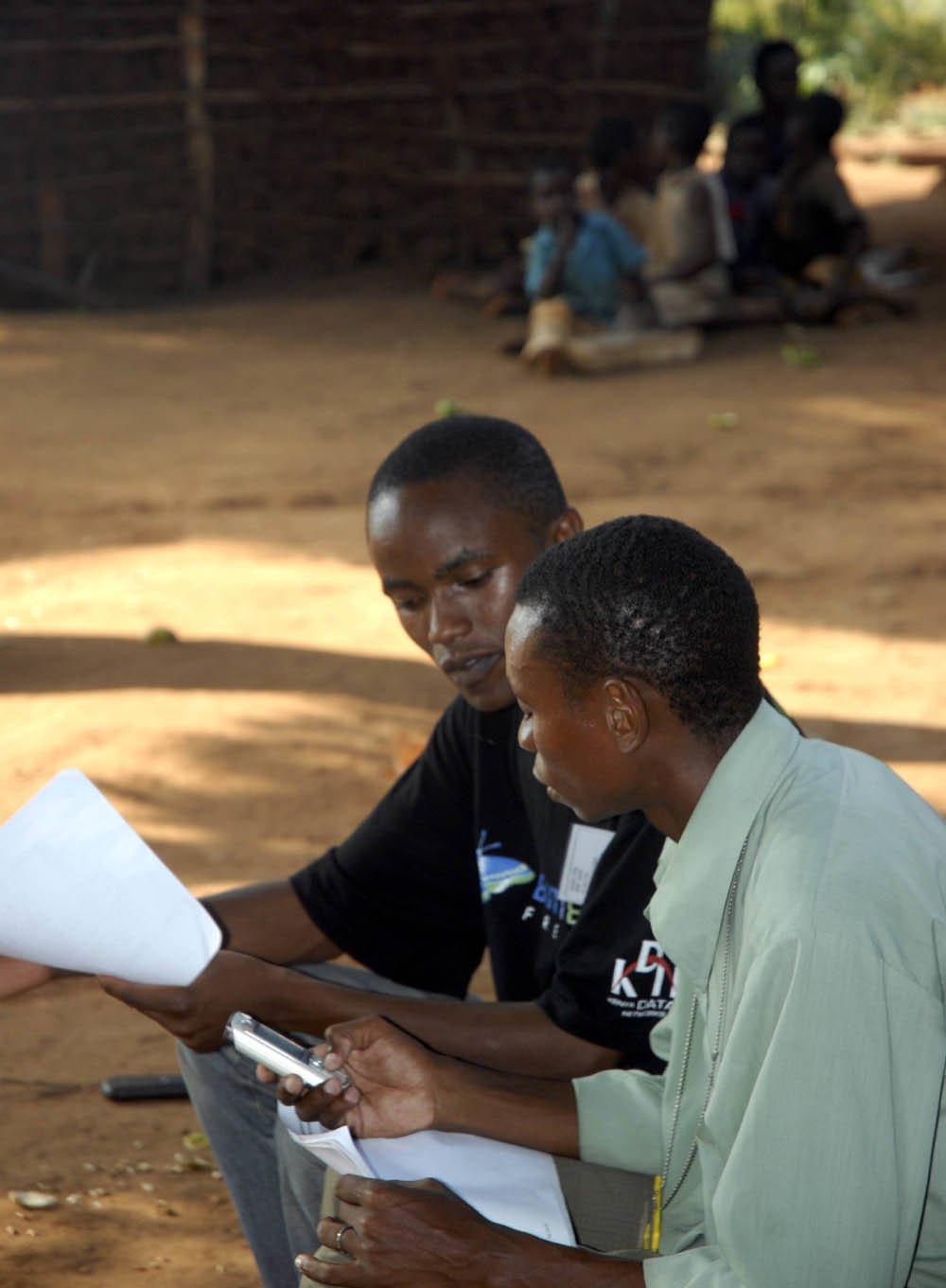 Two men complete fieldwork using a cellphone in Kenya. Image: Flickr/Nathan Eagle/Kiwanja.net