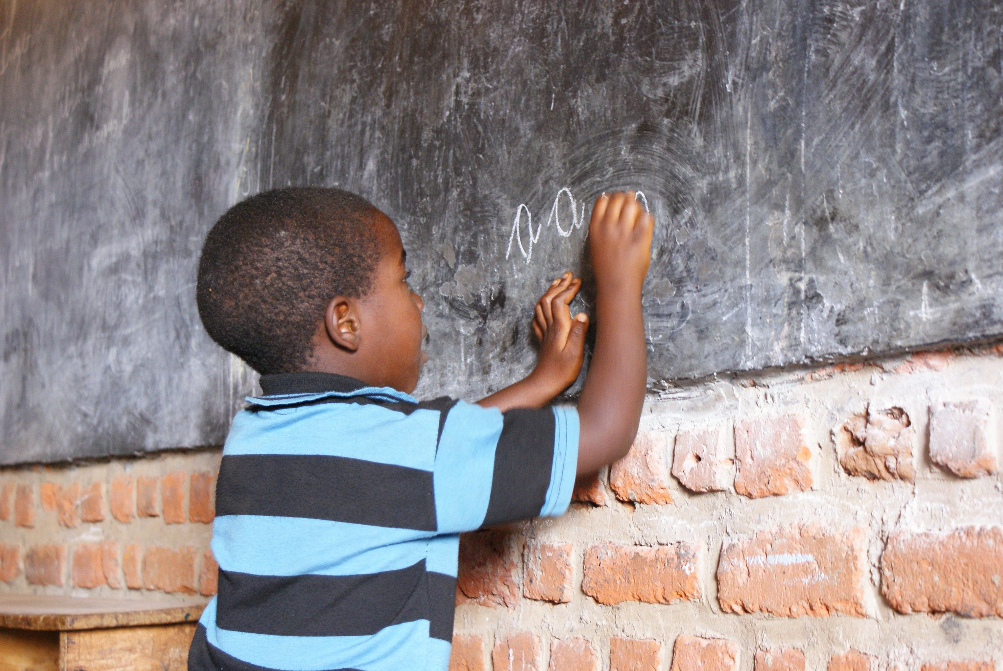 A boy writes on the blackboard in Burundi.jpg