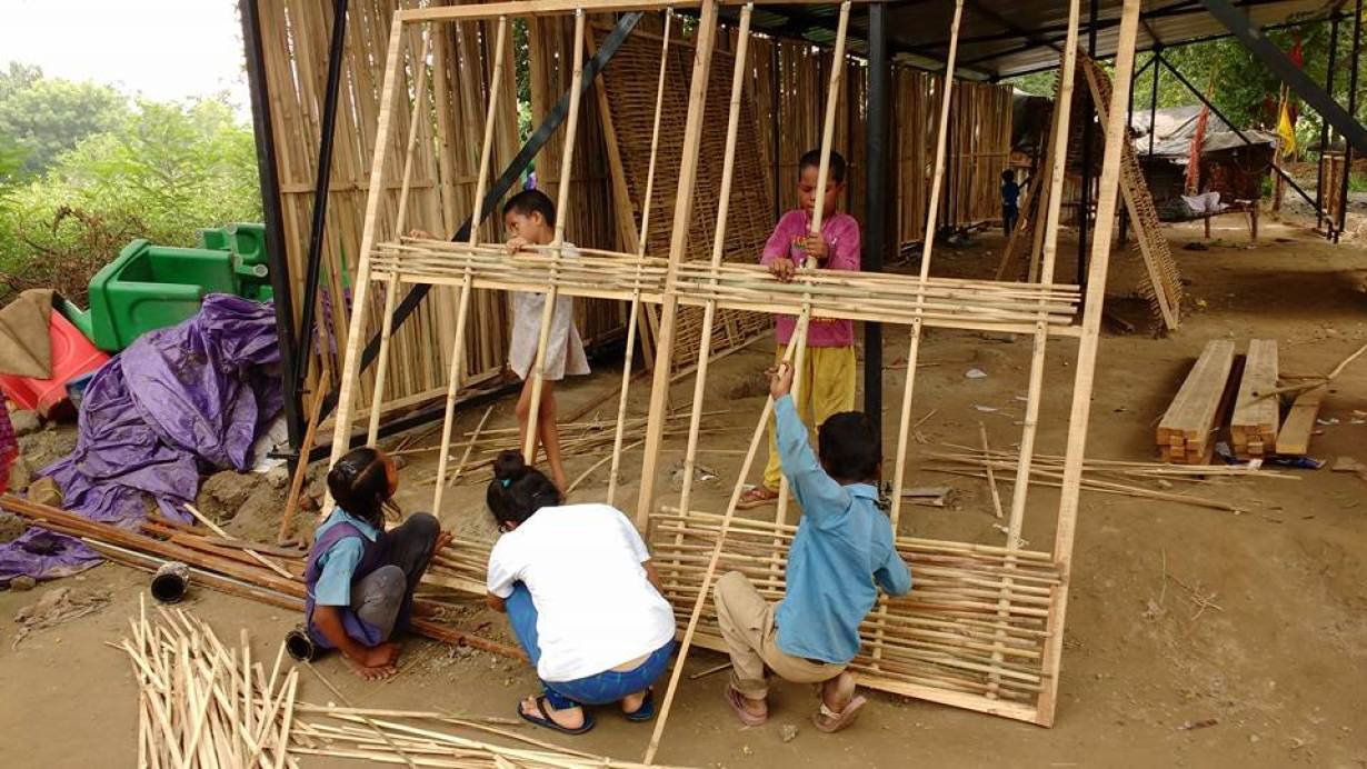Students weaving the walls of the their ModSkool building. The low-cost school for migrant workers' children in Delhi, India, designed by Social Design Collaborative, incorporates local materials such as bamboo and dried grass, and can be easily erected.