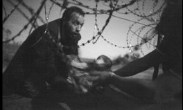 Article: Photo of the year shows refugee father passing son through barbed wire fence