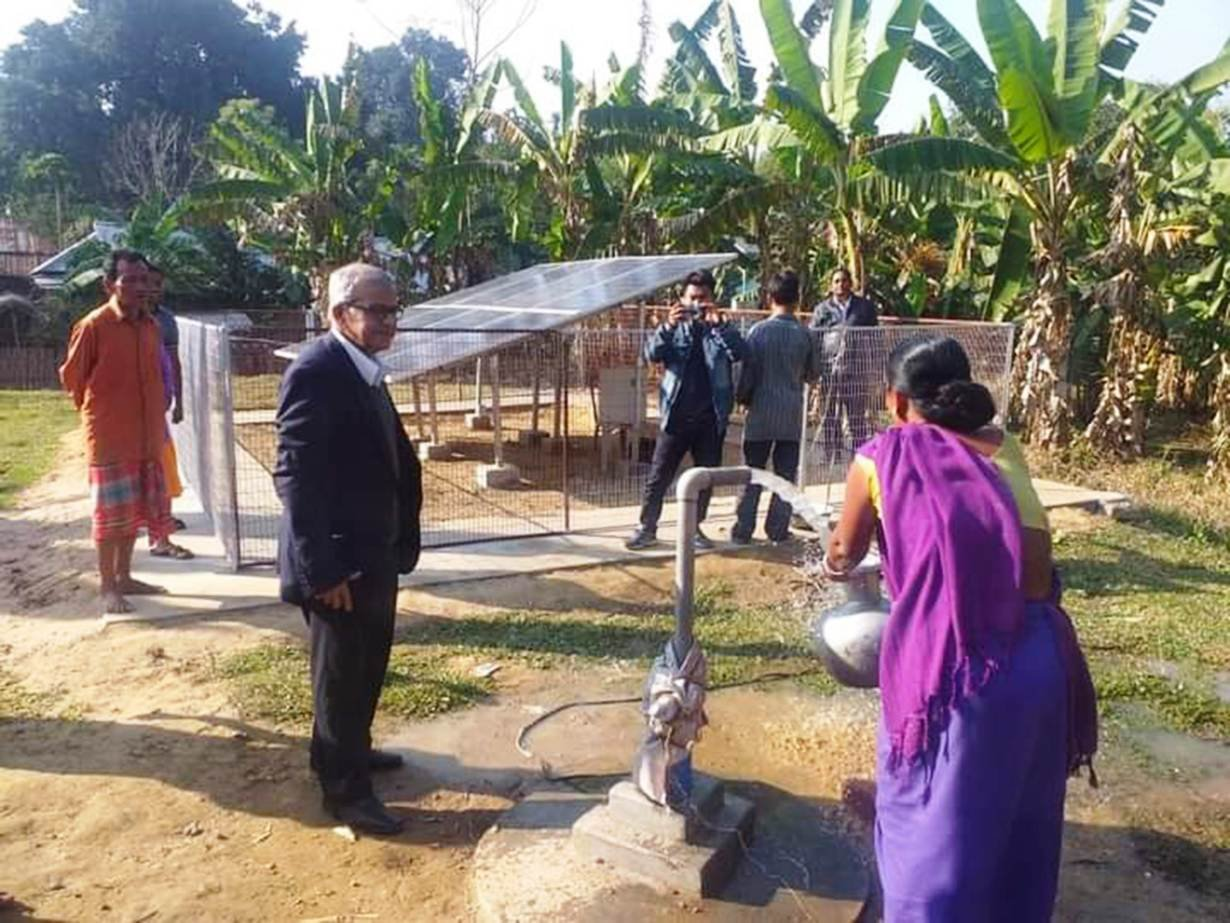 Santipada Gon Chaudhuri with villagers using a solar-powered water pump in Karbongbari village in Tripura, northeastern India, in 2018.